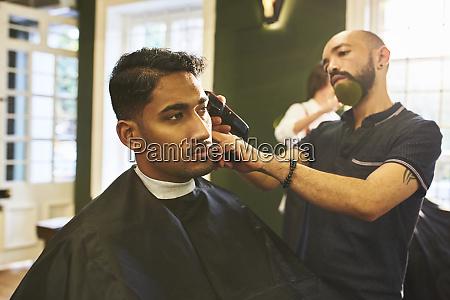 male barber shaving hair of customer