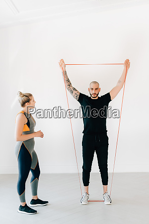 woman observing fitness instructor using resistance