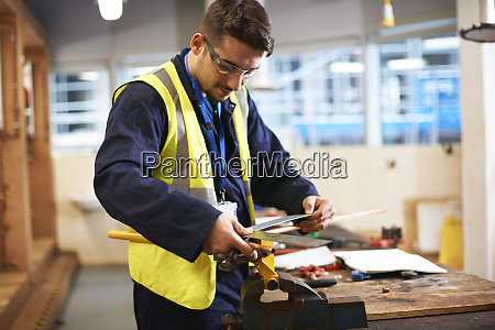 male student using carpenters rule in