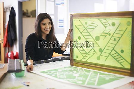 smiling female art student screen printing