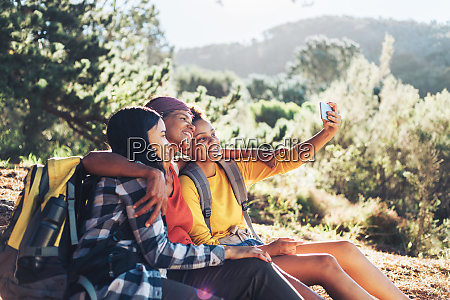 happy mother and daughters taking selfie
