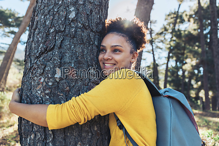 happy carefree young female hiker hugging