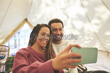 happy couple taking selfie in camping