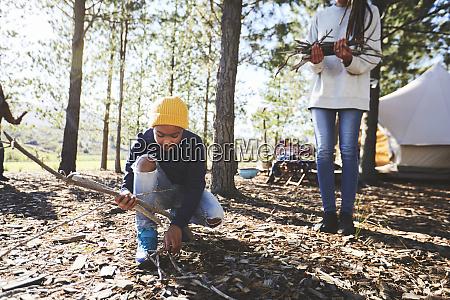 boy picking up sticks for firewood