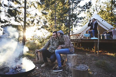 happy couple sitting at campsite campfire