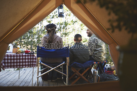 family relaxing outside camping yurt
