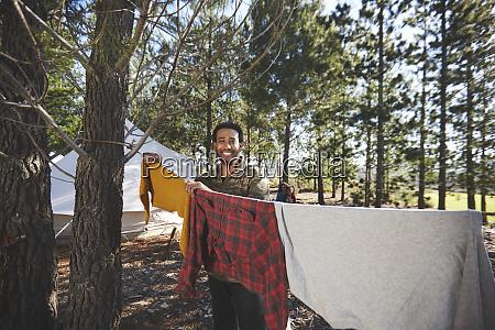 portrait happy man hanging laundry on