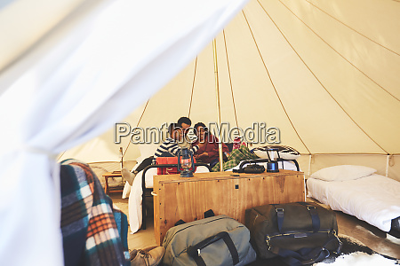 family relaxing on bed inside camping