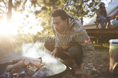 man blowing on campfire in sunny