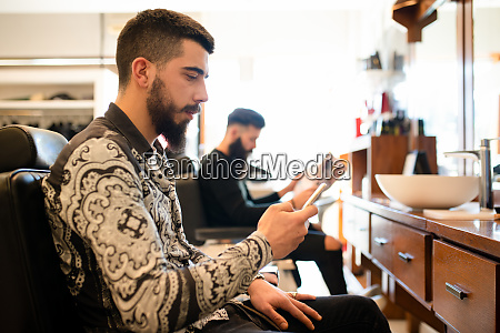 customers waiting and reading in barber
