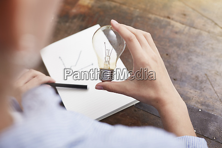 woman with electric bulb planning way