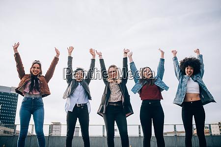 friends raising arms in triumph in