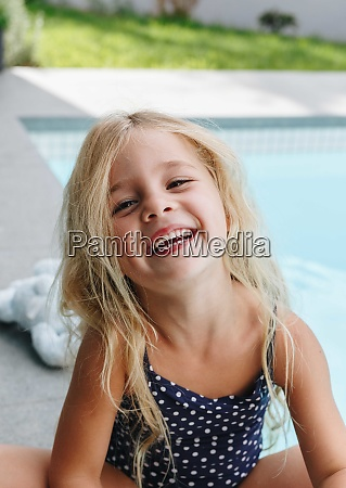happy little girl sitting by swimming