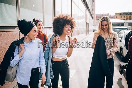friends walking in street milan italy
