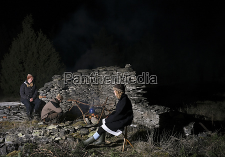 family of three relaxing by campfire