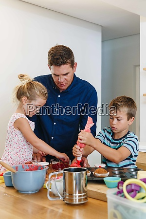 father and children decorating cupcakes with