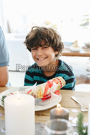 boy smiling at dining table in