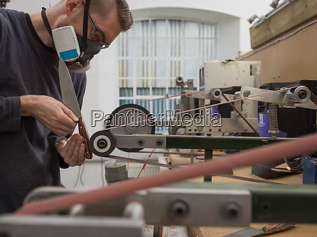 knife factory worker sanding knife handle