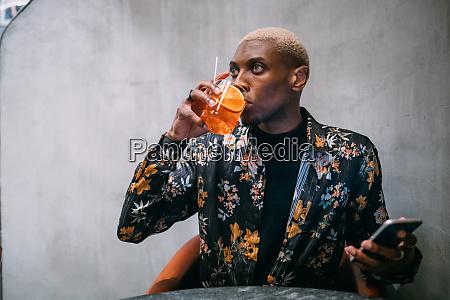 stylish man enjoying drink cellphone in