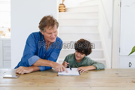 father helping son with homework at