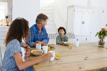 parents watching son smile at breakfast