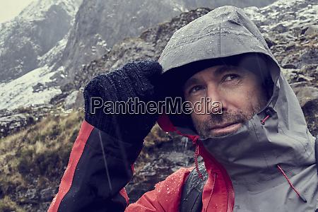 male hiker pulling hood up in