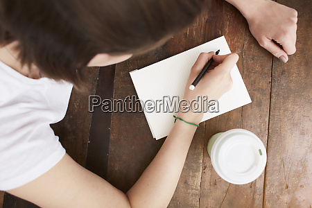 woman writing on notebook at coffee