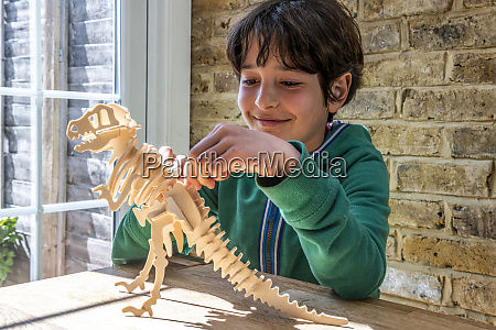 boy playing with wooden dinosaur