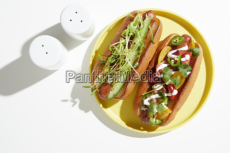 two, garnished, hotdogs, on, yellow, plate, - 27459198
