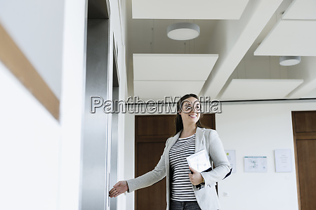 businesswoman with digital tablet pressing button