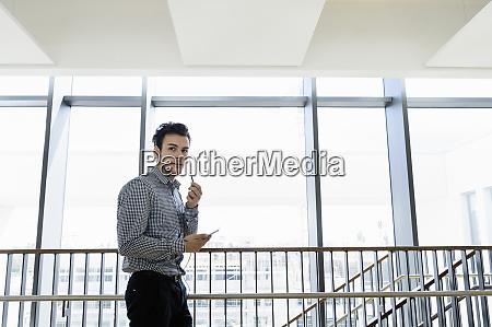 businessman using smartphone in office corridor