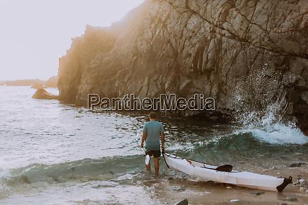 man dragging kayak into sea big