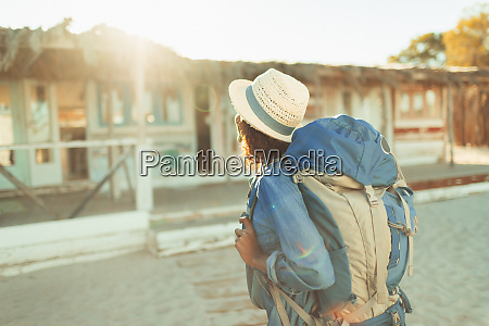 young female backpacker approaching sunny beach