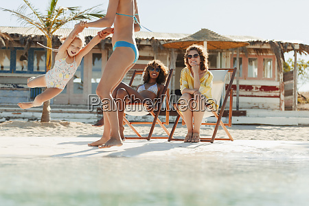 women relaxing and playing with girl