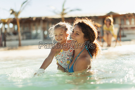 happy mother and daughter swimming in
