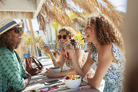 happy women friends eating salad at
