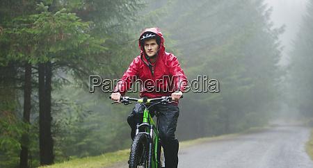 man mountain biking in rain