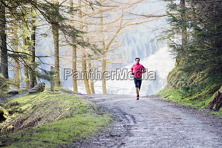 man jogging on trail in woods