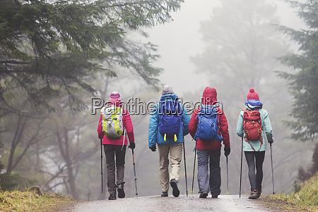 family hiking in rainy woods
