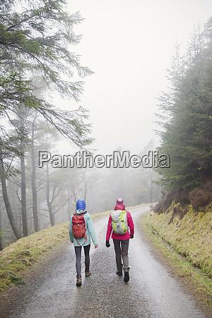 women hiking in rainy woods