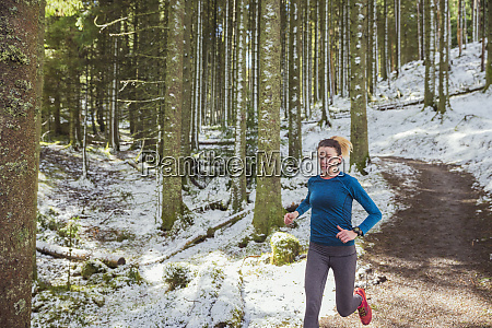 woman jogging in snowy woods