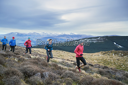 friends jogging on mountain trail