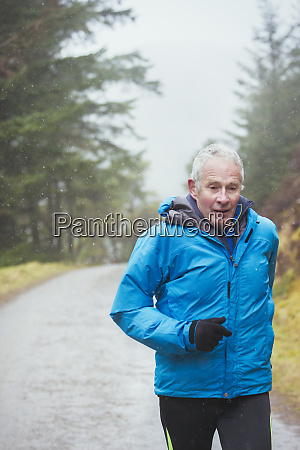 senior man jogging in rain