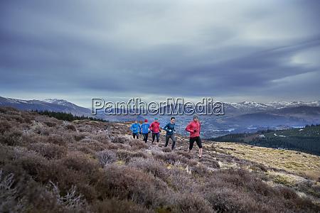 friends jogging along mountain trail