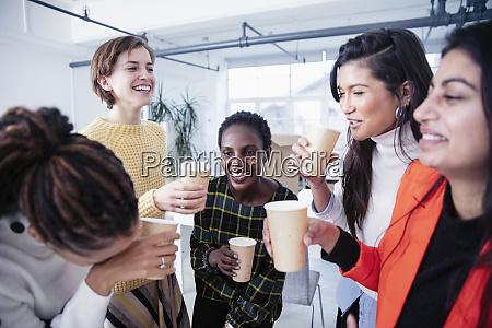happy businesswomen celebrating drinking champagne