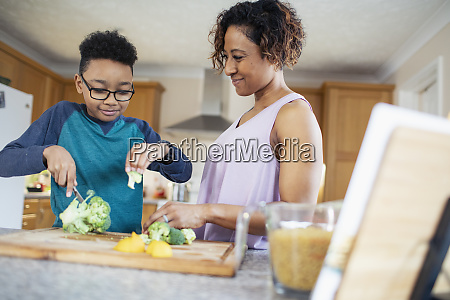 mother and son cooking cutting vegetables