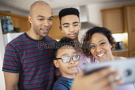family taking selfie in kitchen