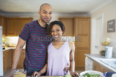 portrait smiling couple cooking in kitchen