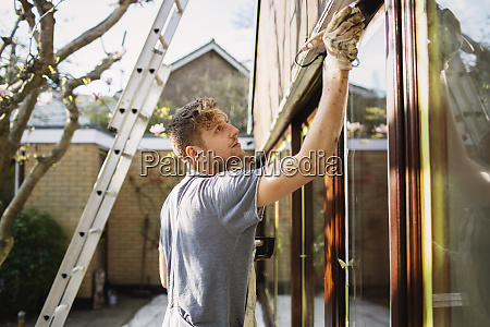 male painter painting home exterior window