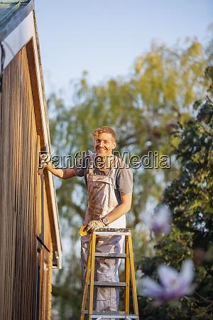 portrait confident male painter on ladder